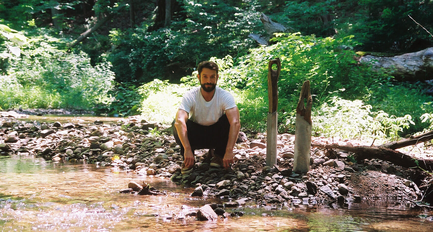 Brad Teasdale crouching on a riverbank with two concrete-and-wood art objects